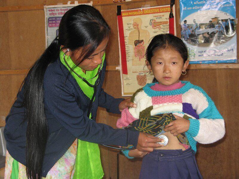 Remote village health centre worker and child
